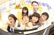 ピアノの前で微笑む保育園児と保育士