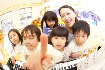 ピアノの周りに集まる保育園児と保育士