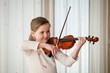 Child playing violin indoors