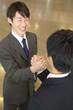 手を組むビジネスマン2人