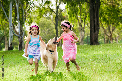 Two young girls running with golden retriever
