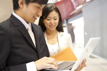 ノートパソコンを触るビジネスマンとOL