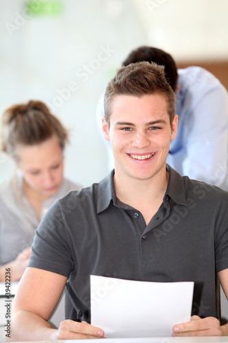 Portrait of student boy doing written exam