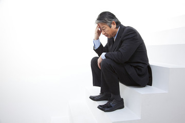 階段で座り込み落ち込むビジネスマン