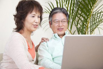 ノートパソコンを触る笑顔のシニアカップル