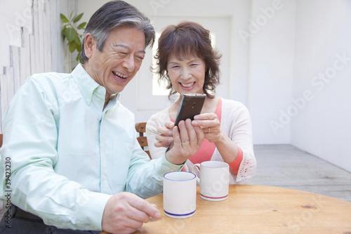 スマートフォンを触る笑顔のシニアカップル