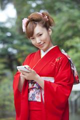 スマートフォンを使う振袖姿の女性