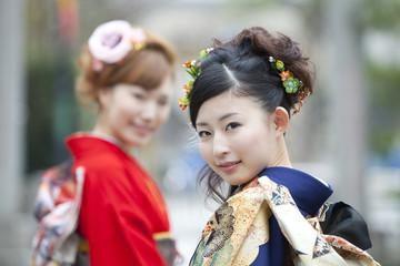 振り返り微笑む振袖姿の女性2人