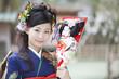 羽子板を持って微笑む振袖姿の女性