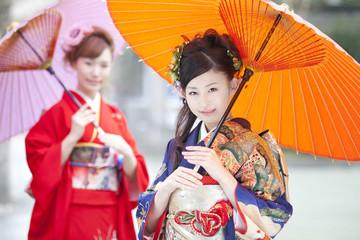 和傘を差す振袖姿の女性2人