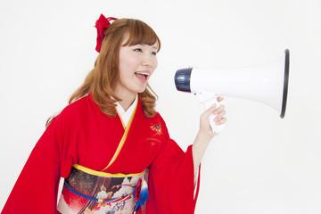メガホンを持って叫ぶ振袖姿の女性