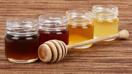 four jars full of honey wooden drizzler, mix taste
