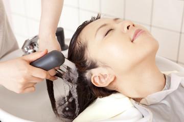美容師にトリートメントを流してもらう女性