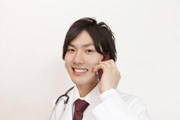 スマートフォンで電話する医師