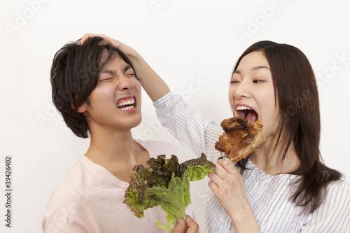 野菜を持った男性と骨付き肉を持った女性