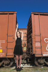 Woman Standing with Railroad Boxcars