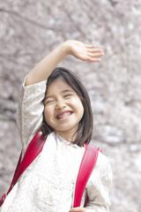桜の下で手を振る小学生女子