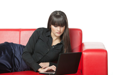 Female having rest on the couch working with laptop