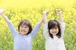菜の花畑で両手を挙げる男の子と女の子
