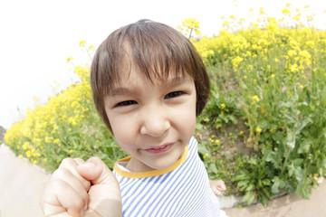 菜の花畑で微笑む男の子