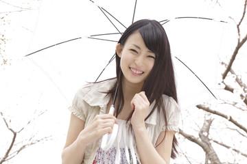 桜の下で日傘を差して微笑む女性