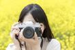 菜の花畑でカメラを構える笑顔の女性