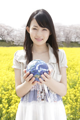 菜の花畑で地球儀を持つ笑顔の女性