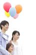 風船を持って微笑む家族