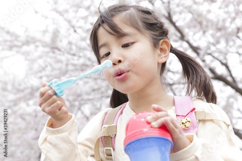 桜の下でシャボン玉を吹く女の子