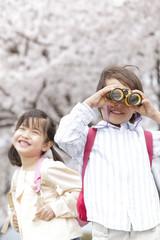 笑顔の女の子と双眼鏡を覗き込む男の子