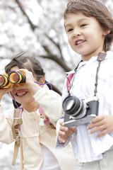 双眼鏡を覗く女の子とカメラを持つ男の子