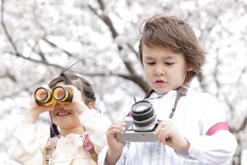 双眼鏡を覗き込む女の子とカメラを持つ男の子