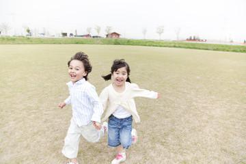 グラウンドを走り回る笑顔の男の子と女の子