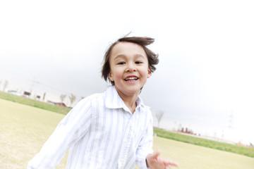 グラウンドを走り回る笑顔の男の子
