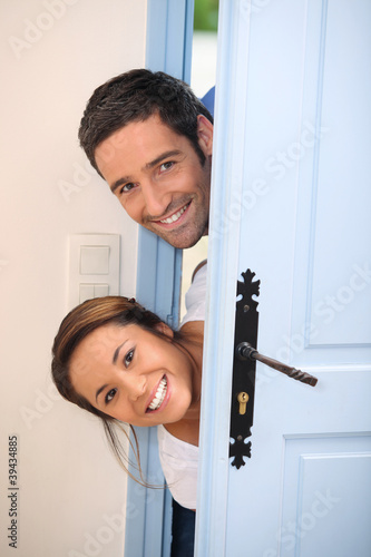 Young couple poking their heads around the front door