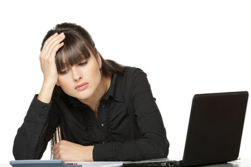Woman with head in hands, looking at calculator exhausted