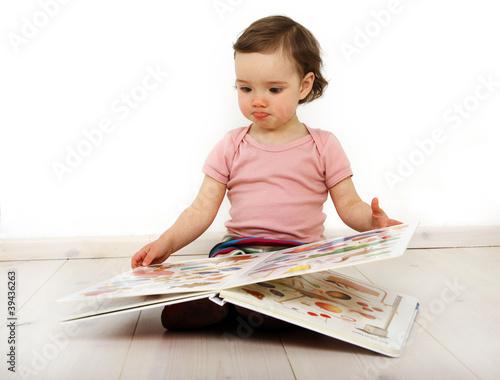 canvas print picture Ein Kind schaut ein Bilderbuch an