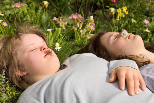 A girl with Down syndrome and her sister resting in the grass.