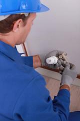 Handyman tightening an adjusting knob.