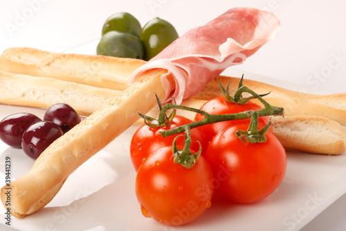 Antipasto con grissini, prosciutto, olive e pomodori