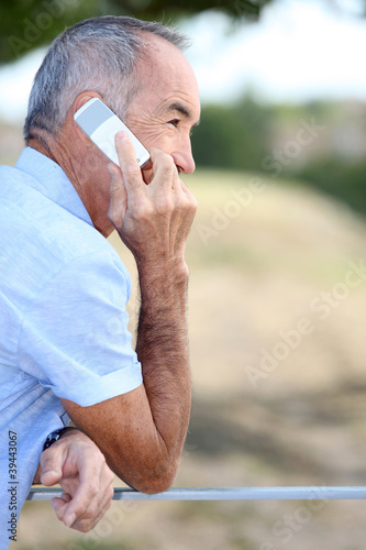 Elderly man talking on his mobile phone outdoors