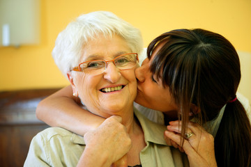 woman kissing a smiling senior woman
