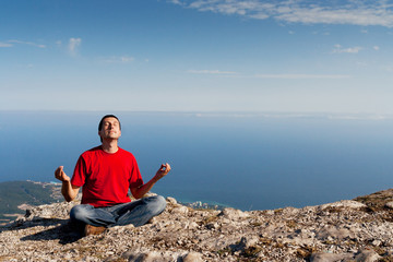 Happy man sits yoga pose on the mountain