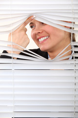 Nosy woman peering through some blinds