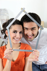 Couple making house shape