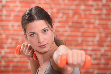Young woman using hand weights in front of a red brick wall
