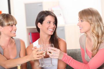 Three housemates drinking wine together