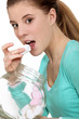 Woman eating marshmallows from jar