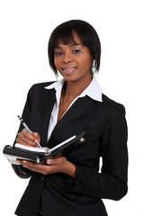 Afro-American businesswoman writing in her agenda