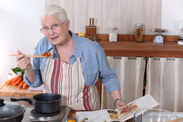 Elderly woman cooking dinner with the help of a recipe